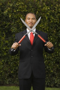 Mixed Race businessman holding pruning shears